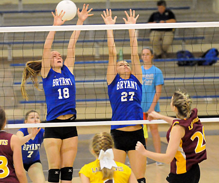 Casey Welch (18) and Grace Camferdam try to get a block. (Photo by Kevin Nagle)