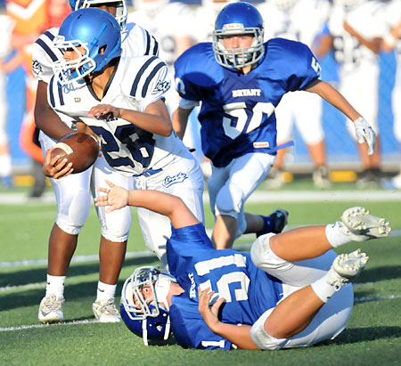 Conway Blue running back Isaiah Duncan (28) tries to get by Bryant White's Christian Del Castillo (51) and Chance Clendening (50). (Photo by Kevin Nagle)