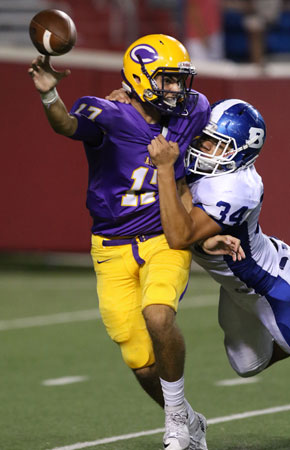 Bryant's Madre Dixon (34) hits Catholic quarterback Taylor Price as he gets rid of the ball. (Photo by Rick Nation)