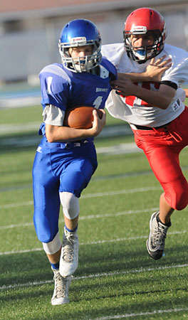 Bethel quarterback Garrett Wilson (1) uses a stiff arm to try to get past Cabot Red's Cody McCoy. (Photo by Kevin Nagle)