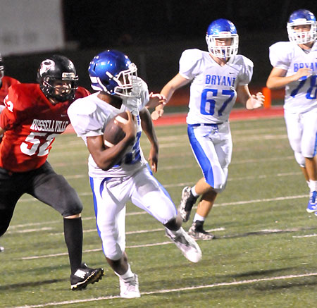 Ahmad Adams sprints upfield off blocks by Brantley Thomas (67) and Brayden Lester (78). (Photo by Kevin Nagle)