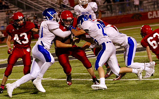 Austin Bailey, left, and William Boyd sandwich a Cabot running back. (Photo by Jon Staton)