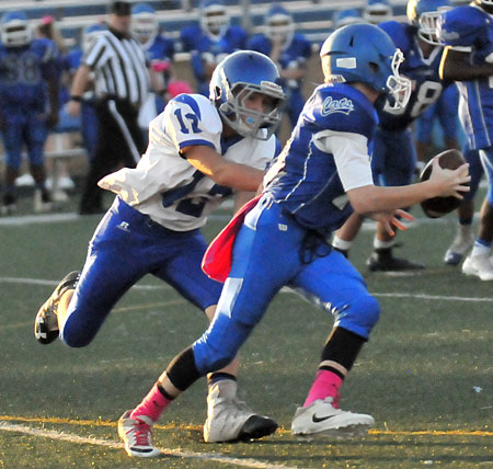 Ethan Andrews (13) chases down Conway White quarterback Ben Weese. (Photo by Kevin Nagle)
