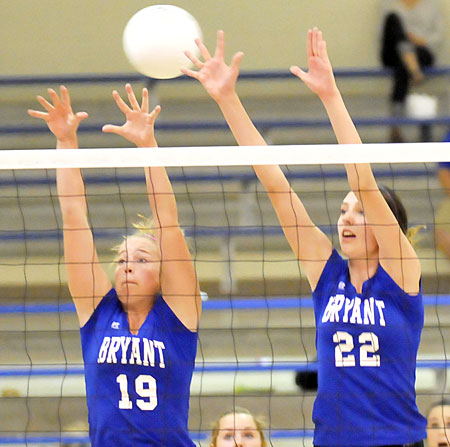Grace Sams (19) and Truli Bates (22) reach for a block. (Photo by Kevin Nagle)