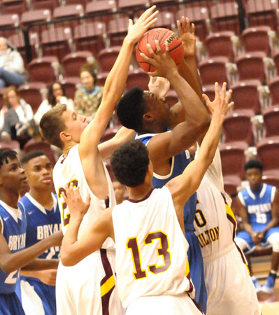 Ahmad Adams fights through a trio of Lake Hamilton defenders to get a shot away. (Photo by Kevin Nagle)
